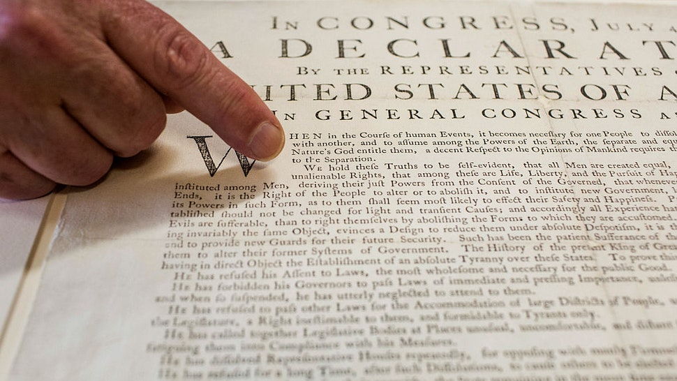 """Peter Drummey, chief reference librarian of the Massachusetts Historical Society, points to a rare copy of the Declaration of Independence, known as a """"Dunlap Broadside,"""" at the society in Boston, Massachusetts, U.S., on Monday, June 29, 2015. Here in acid-free, low humidity stacks are 13 million pages of the personal letters and diaries of men and women who helped create the world we live in. Photographer: Shiho Fukada/Bloomberg via Getty Images"""