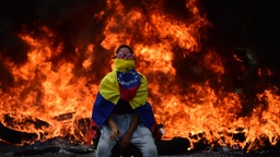 TOPSHOT - A Venezuelan opposition activist is backdropped by a burning barricade during a demonstration against President Nicolas Maduro in Caracas, on April 24, 2017.