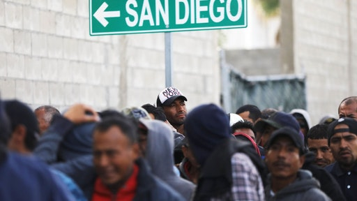 TIJUANA, MEXICO - MARCH 09: Migrants line up for free breakfast at the Desayunador Salesiano Padre Chava shelter and soup kitchen in front of sign for San Diego on March 9, 2018 in Tijuana, Mexico. The soup kitchen receives between 1,000-1,200 migrants daily, most of whom have been deported from the United States. Deportees sometimes end up homeless on the streets of Tijuana. (Photo by Mario Tama/Getty Images)