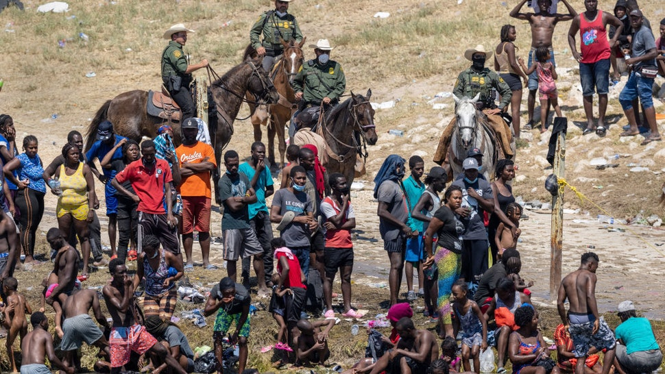 CIUDAD ACUNA, MEXICO - SEPTEMBER 20: Mounted U.S. Border Patrol agents watch Haitian immigrants on the bank of the Rio Grande in Del Rio, Texas on September 20, 2021 as seen from Ciudad Acuna, Mexico. As U.S. immigration authorities began deporting immigrants back to Haiti from Del Rio, thousands more waited in a camp under an international bridge in Del Rio while others crossed the river back into Mexico to avoid deportation. (Photo by John Moore/Getty Images)