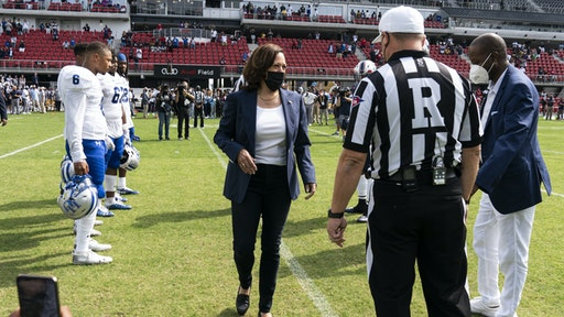 U.S. Vice President Kamala Harris, center, arrives to flip a coin ahead of the Howard University and Hampton University football game at Audi Field in Washington, D.C., U.S., on Saturday, Sept. 18, 2021. The two teams, both historically Black universities, are playing the first-ever Truth and Service Classic game hosted in partnership with Events DC.
