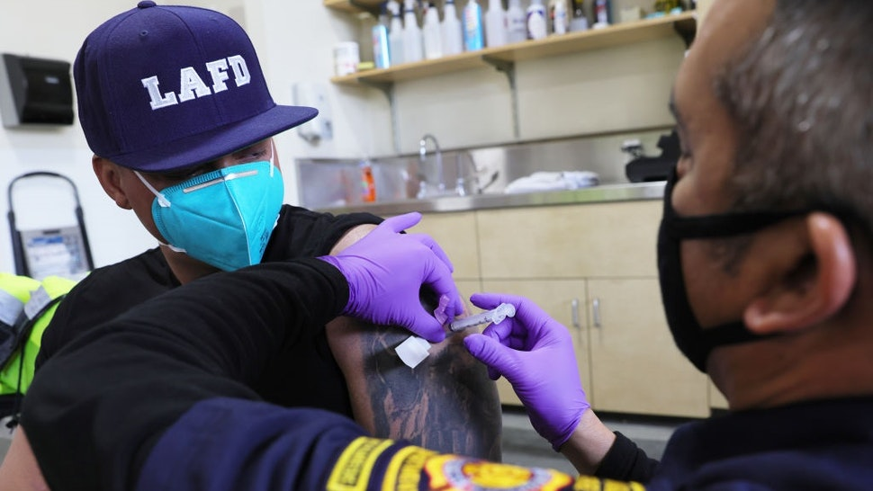 LOS ANGELES, CALIFORNIA - JANUARY 29: A Los Angeles Fire Department (LAFD) firefighter receives a COVID-19 vaccination dose from firefighter paramedic Alexander Gorme (R) at a fire station on January 29, 2021 in Los Angeles, California.