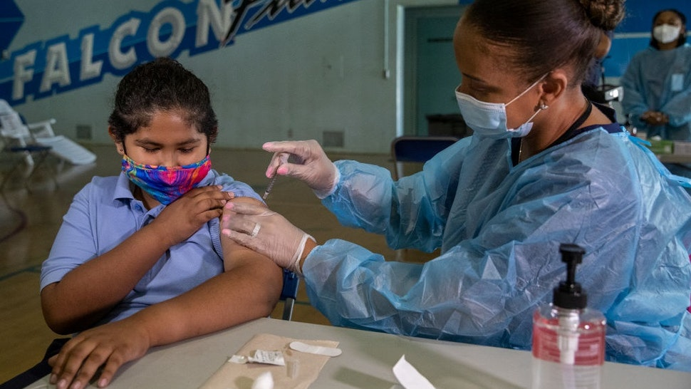SAN FERNANDO, CA - AUGUST 30: Angel Macias, 12, a 7th grader at San Fernando Institute for Applied Media in San Fernando, receives the first dose of the Pfiizer vaccine from Tracy Jones, a licensed vocational nurse.