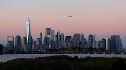 JERSEY CITY, NJ - SEPTEMBER 7: A helicopter flies over the skyline of lower Manhattan and One World Trade Center as the sun sets in New York City on September 7, 2021 as seen from Jersey City, New Jersey.