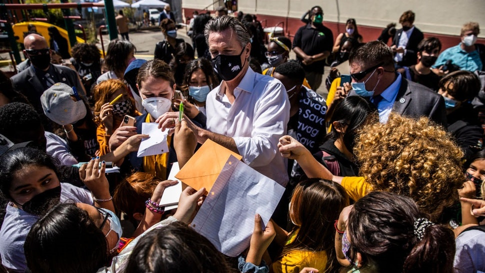 SAN FRANCISCO, CA - SEPTEMBER 15: California Governor Gavin Newsom signs autographs for students during a visit at Melrose Leadership Academy the day after surviving the gubernatorial recall election in Oakland, California on Wednesday, Sept. 15, 2021.