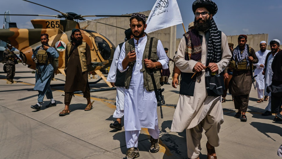 KABUL, AFGHANISTAN -- AUGUST 31, 2021: Anas Haqqani, center right, gets a tour of the military vehicles seized by Taliban fighters after the militant group seized the Hamid Karzai International Airport, in the wake of the American forces completing their withdrawal from the country in Kabul, Afghanistan, Tuesday, Aug. 31, 2021. (MARCUS YAM / LOS ANGELES TIMES)