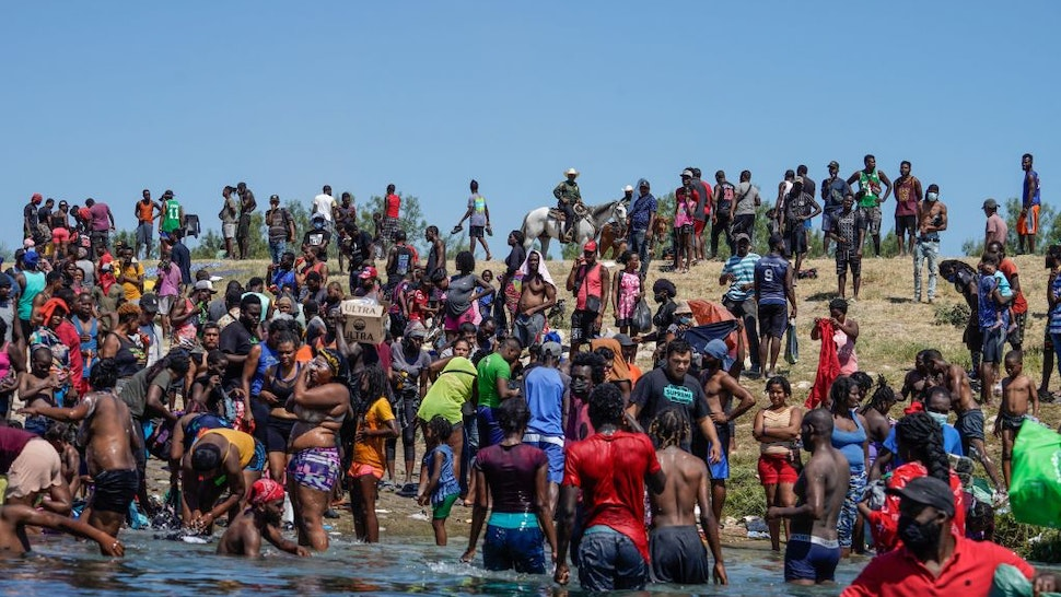 TOPSHOT - Haitian migrants, part of a group of over 10,000 people staying in an encampment on the US side of the border, cross the Rio Grande river to get food and water in Mexico, after another crossing point was closed near the Acuna Del Rio International Bridge in Del Rio, Texas on September 19, 2021. - The United States said Saturday it would ramp up deportation flights for thousands of migrants who flooded into the Texas border city of Del Rio, as authorities scramble to alleviate a burgeoning crisis for President Joe Biden's administration. (Photo by PAUL RATJE / AFP) (Photo by
