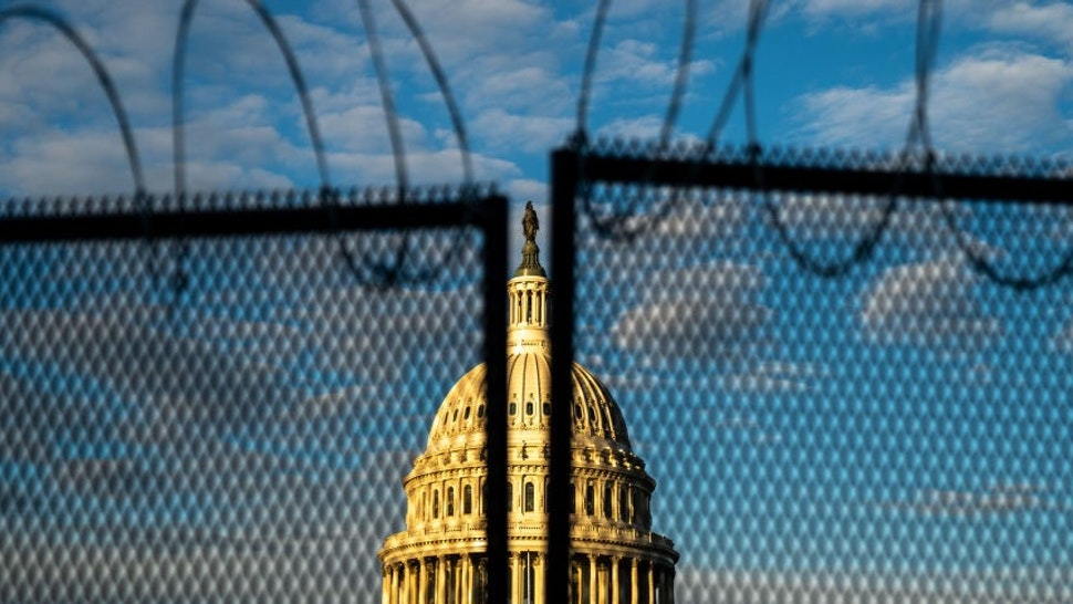 WASHINGTON, DC - JANUARY 16: Barbed wire, is seen atop security fencing, with the dome of the U.S. Capitol Building on Saturday, Jan. 16, 2021 in Washington, DC. After last week's riots and security breach at the U.S. Capitol Building, the FBI has warned of additional threats in the nation's capital and across all 50 states. (