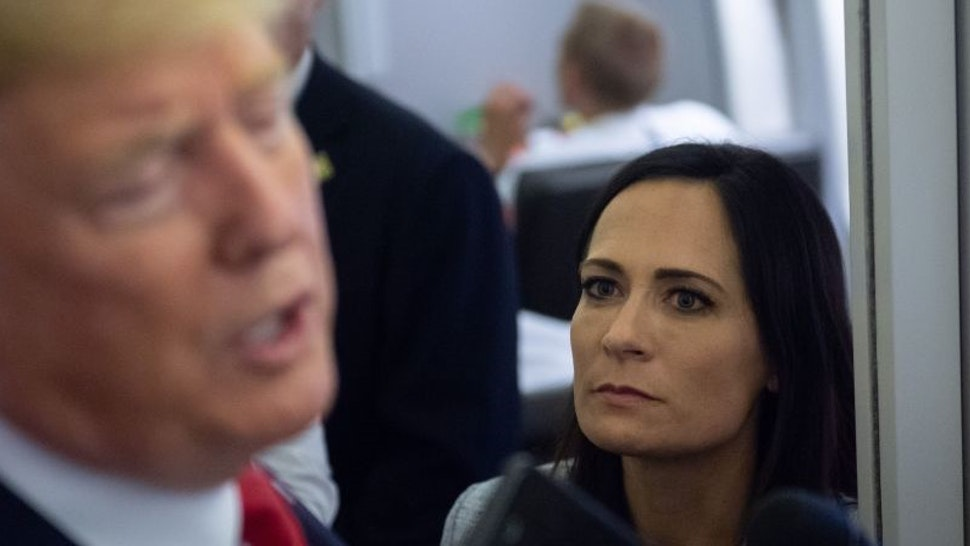 White House Press Secretary Stephanie Grisham listens as US President Donald Trump speaks to the media aboard Air Force One while flying between El Paso, Texas and Joint Base Andrews in Maryland, August 7, 2019. (Photo by SAUL LOEB / AFP) (Photo credit should read