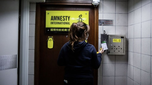 HONG KONG-CHINA-POLITICS-RIGHTS-AMNESTY A woman is seen at the entrance to Amnesty International offices in Hong Kong on October, 2021, as the Human Rights organisation announces it will be closing its offices by the end of 2021 citing Beijings enacted national security law as a reason. (Photo by ISAAC LAWRENCE / AFP) (Photo by ISAAC LAWRENCE/AFP via Getty Images) ISAAC LAWRENCE / Contributor
