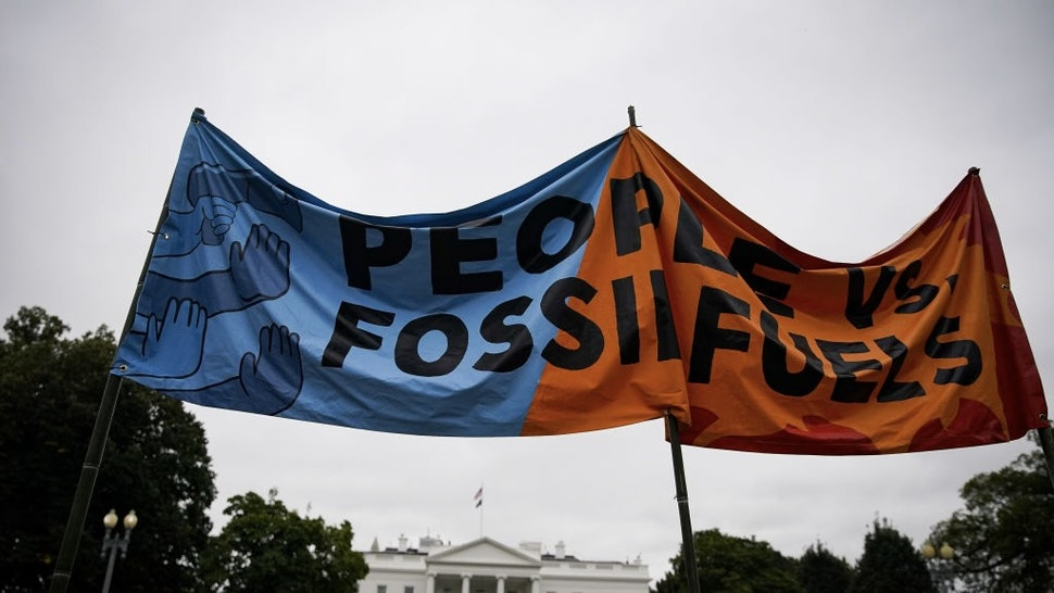 """WHO Says Climate Change Is Single Biggest Health Threat Demonstrators hold a """"People Vs. Fossil Fuels"""" banner during a climate change protest on Indigenous Peoples' Day outside the White House in Washington, D.C., U.S., on Monday, Oct. 11, 2021. Climate change is the single biggest health threat that humanity faces as extreme weather events kill thousands and weakens healthcare systems where they are needed the most, according to a new report by the World Health Organization. Photographer: Al Drago/Bloomberg via Getty Images Bloomberg / Contributor"""