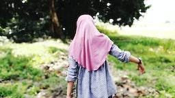 Rear View Of Girl Wearing Hijab Walking On Field - stock photo