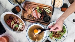 Top view of dishes served on a table. The diner's hand is seen scooping the ingredient from the bowl of soup.