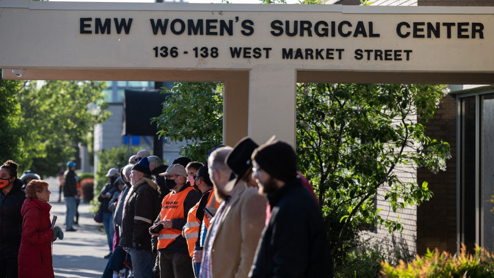 LOUISVILLE, KY - MAY 08: Pro-life demonstrators and clinic escorts stand in front of the EMW Womens Surgical Center, an abortion clinic, on May 8, 2021 in Louisville, Kentucky. Various anti-abortion religious groups and members of pro-life organizations gathered on the sidewalk near the clinic to wish approaching patients a happy Mother's Day and convince them not to enter. (Photo by Jon Cherry/Getty Images)