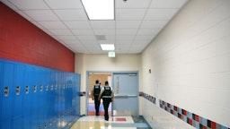 Alexandria Police Department school resource officers, Johnny Larios, left center, and Gary Argueta, right center, walk through a hallway at T.C. Williams High School on Wednesday June 09, 2021 in Alexandria, VA.