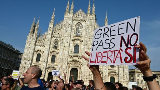 """Protesters take part in a demonstration on Piazza Duomo in Milan on July 24, 2021, against the introduction of a mandatory 'green pass' for indoor dining and entertainment area, in the aim to limit the spread of the Covid-19. - Italy on July 22 said a health pass would be mandatory for people wishing to access bars, restaurants, swimming pools, sports facilities, museums and theatres from August 6. The rapid spread of the highly contagious Delta variant has fueled a surge in Covid-19 cases around the world this week, with total cases hitting 192,942,266 with 4,143,687 deaths. The placard reads """"Green Pass No, Freedom Yes"""". (Photo by MIGUEL MEDINA / AFP) (Photo by MIGUEL MEDINA/AFP via Getty Images)"""