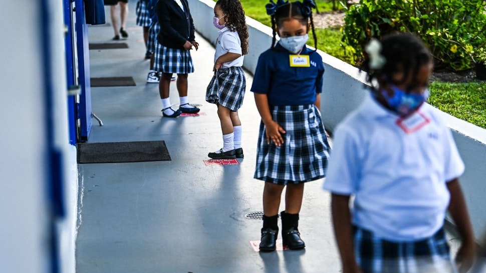 Students wear facemasks and stand in a social distance on their first day of school after summer vacation at the St. Lawrence Catholic School in north of Miami, on August 18, 2021. (Photo by CHANDAN KHANNA / AFP) (Photo by CHANDAN KHANNA/AFP via Getty Images)