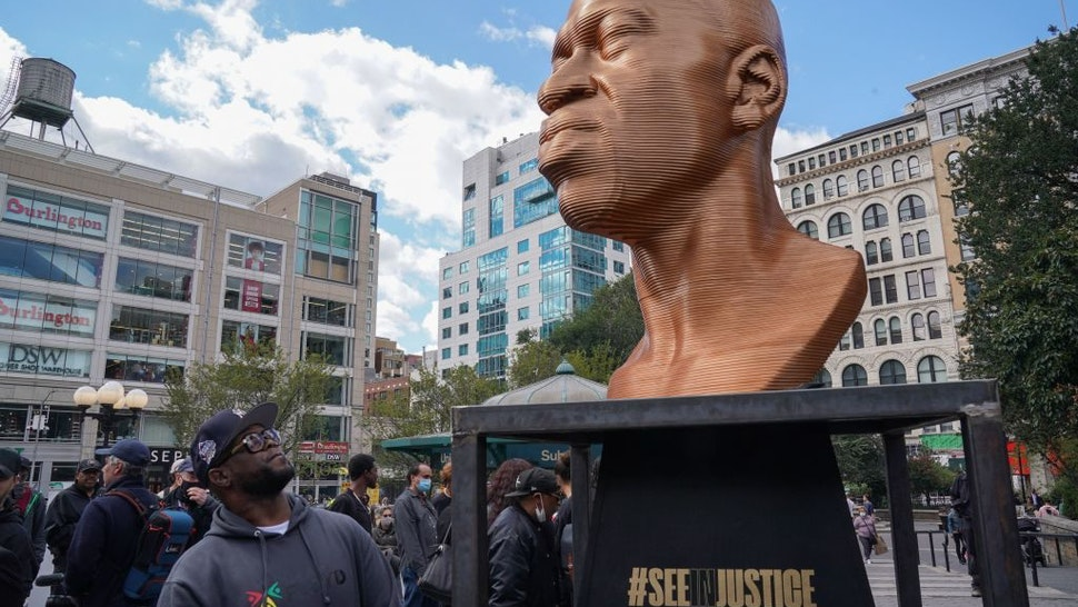 A man looks at a George Floyd statue as the Immersive art organization, Confront Art, in collaboration with the NYC Parks, unveils the SEENINJUSTICE exhibit, featuring three sculptures by Chris Carnabucci