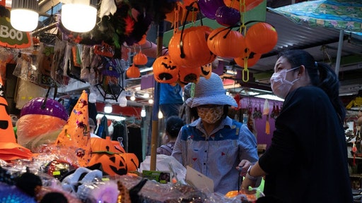 A customer (R) browses through seasonal halloween props at a stall in Hong Kong on October 16, 2021.