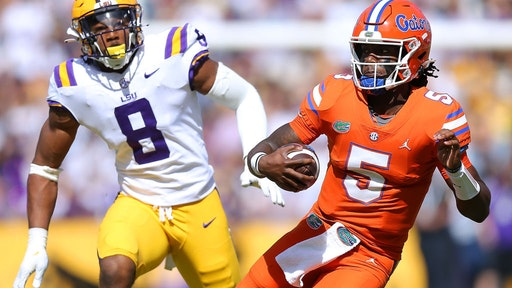 Emory Jones #5 of the Florida Gators runs with the ball as BJ Ojulari #8 of the LSU Tigers defends during the first half at Tiger Stadium on October 16, 2021 in Baton Rouge, Louisiana.