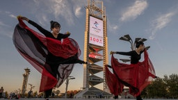 BEIJING, CHINA - OCTOBER 27: Women practice a dance routine in front of a large countdown screen showing 100 days before the opening of the Beijing 2022 Winter Olympics at the Olympic Park on October 27, 2021 in Beijing, China. The games are set to open on February 4, 2022. (Photo by Kevin Frayer/Getty Images)