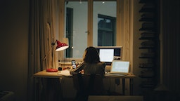 Girl using laptop and computer while sitting at illuminated desk - stock photo