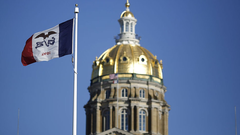 The Iowa state flag flies outside the State Capitol Building in Des Moines, Iowa, U.S., on Friday, Jan. 29, 2016. As the first in the nation Iowa caucuses approaches, where registering your vote isn't as simple as casting a ballot, the state is starting to thrum with nervous energy.