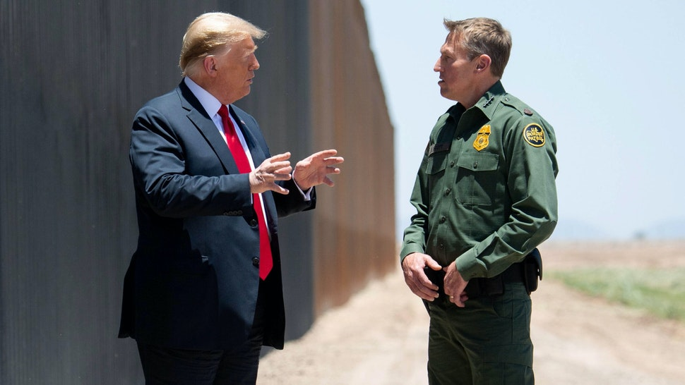 US President Donald Trump speaks with US Border Patrol Chief Rodney Scott (R) as they participates in a ceremony commemorating the 200th mile of border wall at the international border with Mexico in San Luis, Arizona, June 23, 2020.