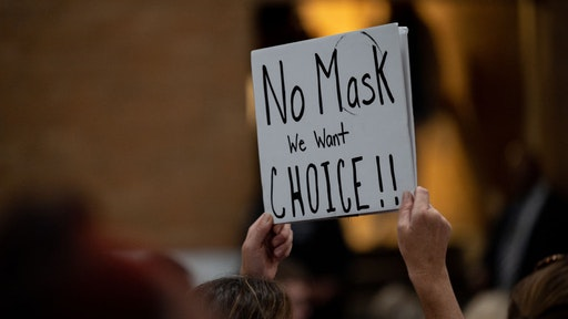 A demonstrator holds a sign protesting against mask mandates during a school board meeting for the Jefferson County Public Schools district in Louisville, Kentucky, U.S., on Tuesday, July 27, 2021. The Centers for Disease Control and Prevention recommends that teachers, staff, students and visitors to K-12 schools wear masks indoors regardless of vaccination status, according to guidance released today. Photographer: Jon Cherry/Bloomberg via Getty Images
