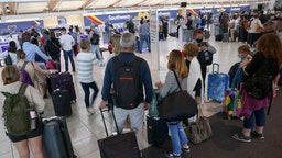 BALTIMORE, MARYLAND - OCTOBER 11: Travelers wait to check in at the Southwest Airlines ticketing counter at Baltimore Washington International Thurgood Marshall Airport on October 11, 2021 in Baltimore, Maryland. Southwest Airlines is working to catch up on a backlog after canceling hundreds of flights over the weekend, blaming air traffic control issues and weather.