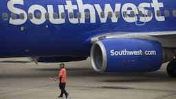 A worker directs a Southwest Airlines Co. Boeing 737 passenger jet pushing back from a gate at Midway International Airport (MDW) in Chicago, Illinois, U.S., on Monday, Oct. 11, 2021. Southwest Airlines Co.disruptions moved into a fourth day, with 355 canceled flights, or 10% of its daily schedule, on Monday, the latest in a series of setbacks at the carrier.