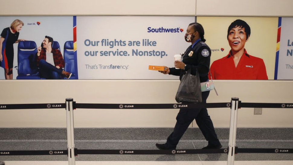 A Transportation Security Administration (TSA) officer walks past Southwest Airlines Co. signage at Midway International Airport (MDW) in Chicago, Illinois, U.S., on Monday, Oct. 11, 2021. Southwest Airlines Co.disruptions moved into a fourth day, with 355 canceled flights, or 10% of its daily schedule, on Monday, the latest in a series of setbacks at the carrier.