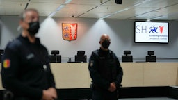 """Judicial officers stand in the empty court room of the Langericht Itzehoe court prior to a trial against a 96-year-old former secretary for the SS commander of the Stutthof concentration camp at the court room in Itzehoe, northern Germany, on September 30, 2021. - The woman failed to turn up for the start of her trial, the judge said, issuing an arrest warrant for the """"fugitive"""". (Photo by Markus Schreiber / POOL / AFP)"""