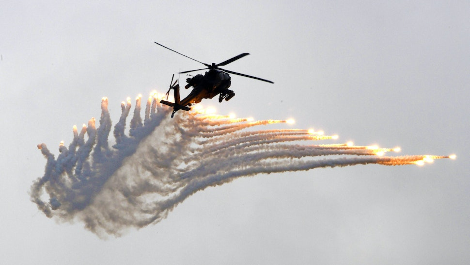 An AH-64 Apache attack helicopter releases flares during the Han Kuang drill at the Ching Chuan Kang (CCK) air force base in Taichung, central Taiwan, on June 7, 2018. - Taiwan on June 7 staged its largest annual drills simulating Chinese attacks as Beijing stepped up military and diplomatic pressure on the island amid growing tensions.