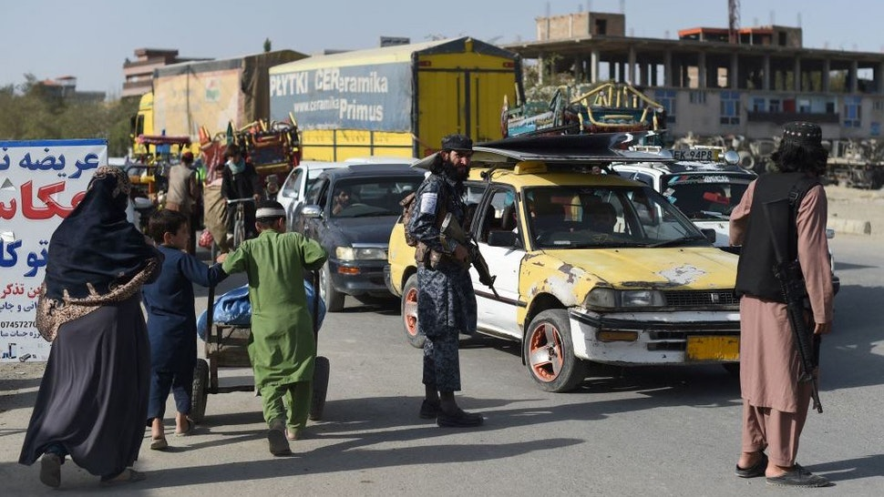 In this picture taken on October 3, 2021, Taliban fighters working as a police force check commuters at a road checkpoint in Kabul. - The Taliban's new police force already counts about 4,000 men in the capital, says a Kabul police spokesman, insisting the city is far safer than before, as the hardline group builds a police force from scratch. - TO GO WITH Afghanistan-police-Taliban,FOCUS by Elise BLANCHARD (Photo by WAKIL KOHSAR / AFP) / TO GO WITH Afghanistan-police-Taliban,FOCUS by Elise BLANCHARD (Photo by WAKIL KOHSAR/AFP via Getty Images)