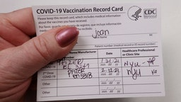 In this photo illustration,Patient holding Covid 19 vaccinated record card.