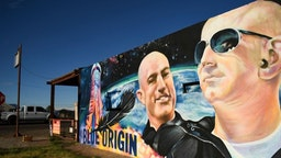 TOPSHOT - A pickup truck drives past a mural of billionaire Amazon founder Jeff Bezos (R) and his brother Mark Bezos with a Blue Origin rocket in Van Horn, Texas on October 11, 2021. - Blue Origin is scheduled to launch the New Shepard NS-18 mission to space with passengers including actor William Shatner on October 13 from West Texas, near Van Horn. (Photo by Patrick T. FALLON / AFP) (Photo by