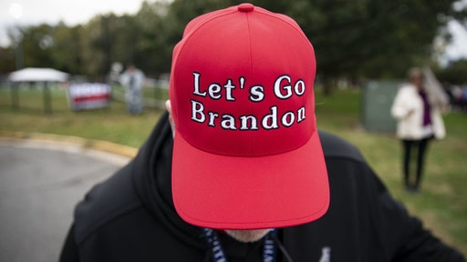 """A supporter of former U.S. President Donald Trump displays a """"Let's Go Brandon"""" hat before a campaign event for Terry McAuliffe, Democratic gubernatorial candidate for Virginia, in Arlington, Virginia, U.S., on Tuesday, Oct. 26, 2021. McAuliffe, a former Virginia governor is locked in a dead heat with Glenn Youngkin, a former co-chief executive officer of Carlyle Group Inc., ahead of next week's election. Photographer"""