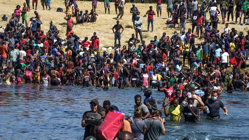 Haitian migrants, part of a group of over 10,000 people staying in an encampment on the US side of the border, cross the Rio Grande river to get food and water in Mexico, after another crossing point was closed near the Acuna Del Rio International Bridge in Del Rio, Texas on September 19, 2021. - The United States said Saturday it would ramp up deportation flights for thousands of migrants who flooded into the Texas border city of Del Rio, as authorities scramble to alleviate a burgeoning crisis for President Joe Biden's administration.